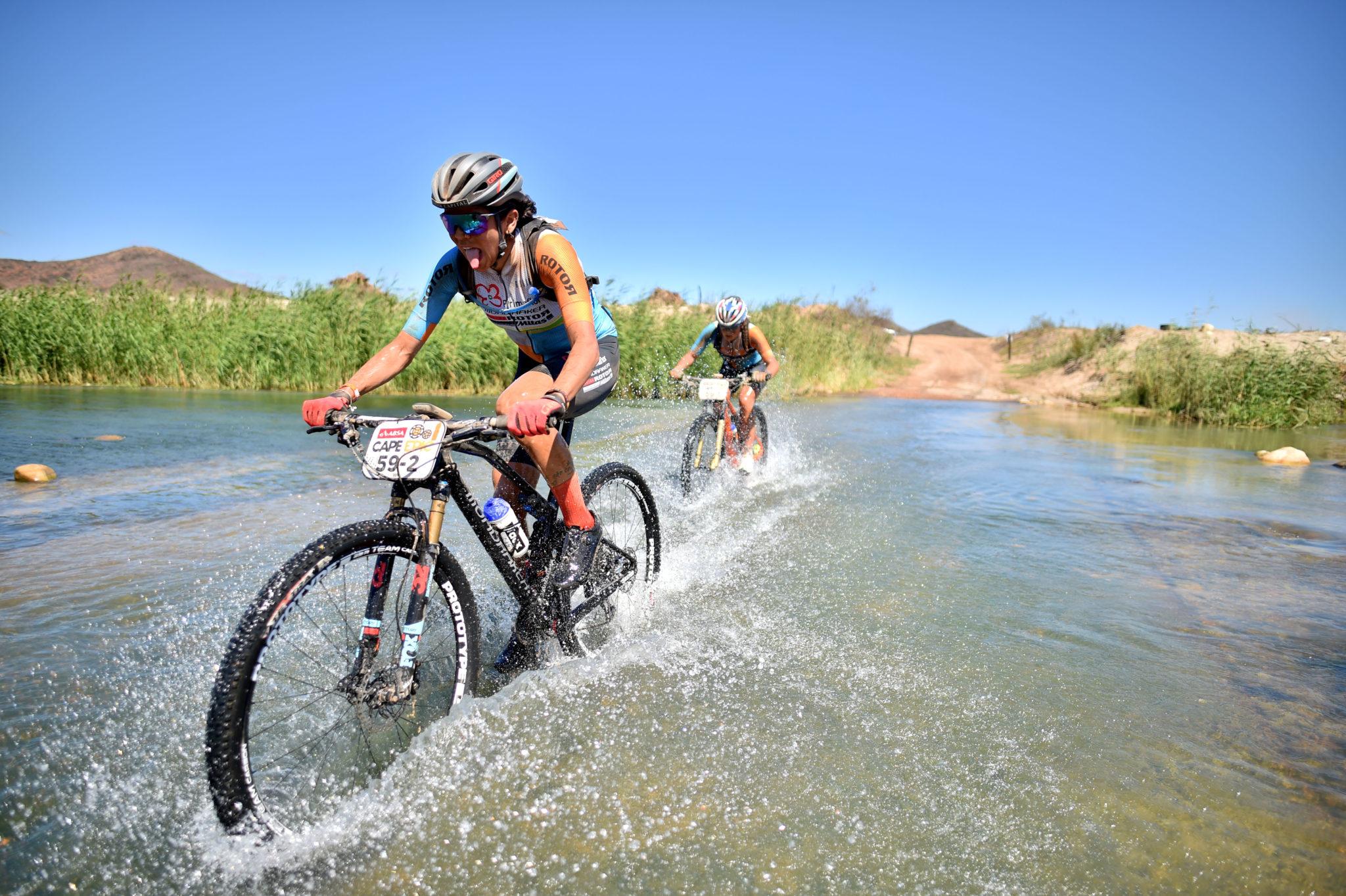 Raiza e Margot cruzam rio no fim da etapa (Bernhard Glessing / Sportograf)